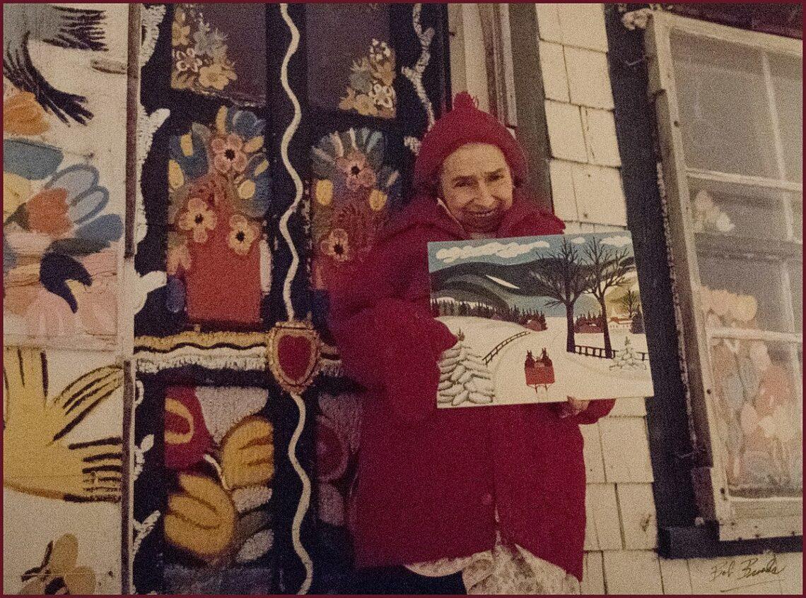 Frau in rotenem Mantel und roter Mütze hält ein Winterbild (Schnee, Schlitten, Straße, Berge) und lächelt zur Kamera. Hintergrund in bunten Farben, Vögel, Blumen, Ornamente. Rechts ein Fenster.
