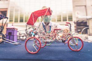 Miniatur-Fahrradrikscha auf einem Tisch, im Hintergrund unscharf ein Mensch mit Gesichtsmaske; weiter Miniaturräder.