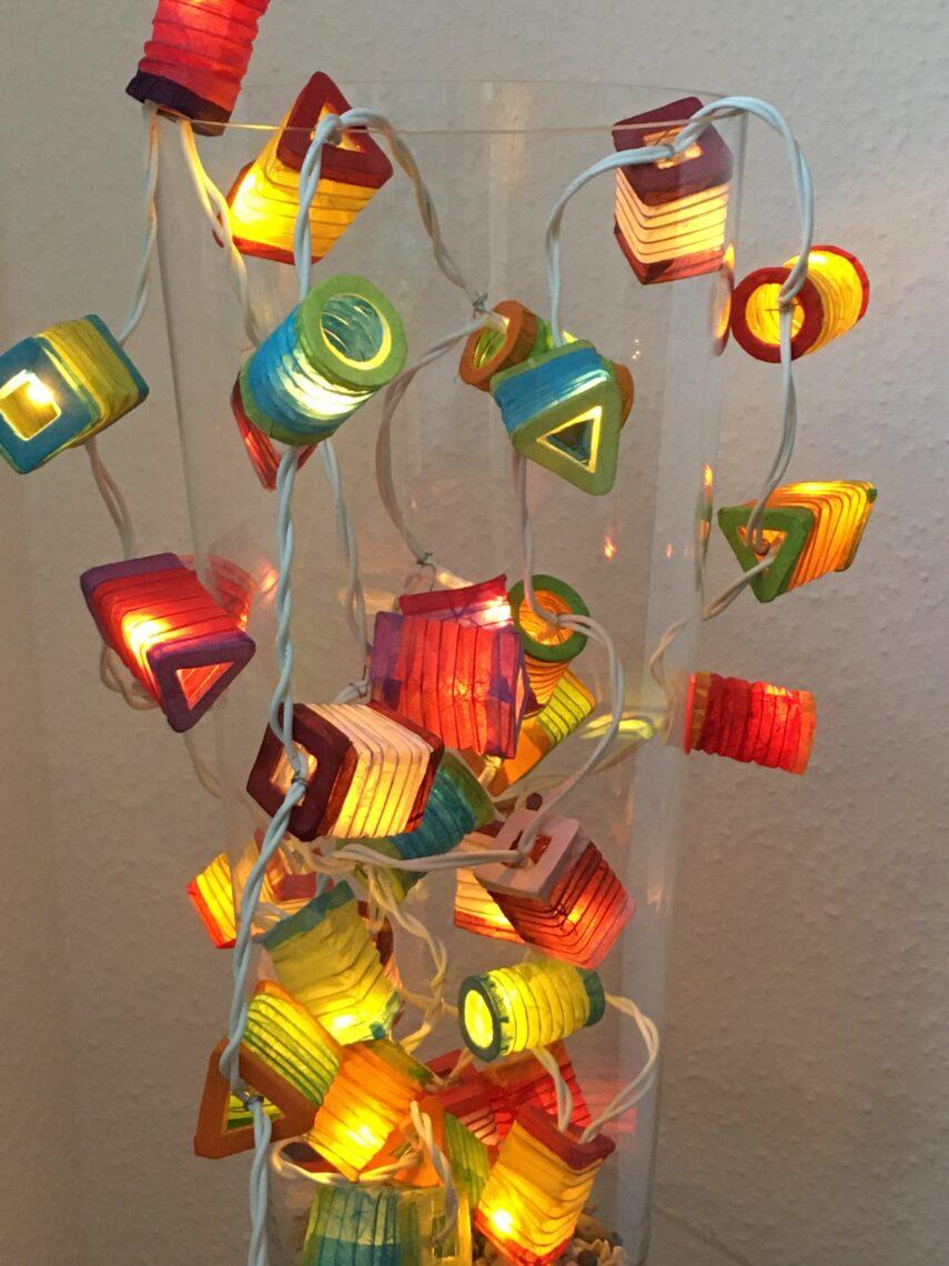 Lampions. Klein, bunt und eckig. An einem Kabel in eine hohe Glasvase drapiert. Leuchtend. cc-by-sa-4.0 Gerhard Ditscheid
