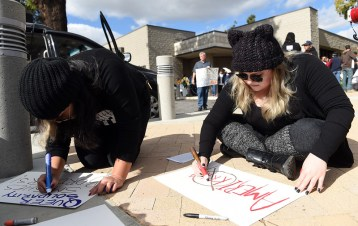 "Alma Trejo, of Montclair, left, and Jessica Alcocer, of Alhambra, make signs as about 200 protestors gather to march through downtown during a ""United Against the Trump Agenda"" event in Ontario, CA., Saturday, January 21, 2017. (Staff photo by Jennifer Cappuccio Maher/Inland Valley Daily Bulletin/SCNG)"