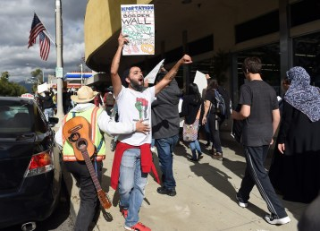 "Fernando Romero, of Upland, with the Pomona Economic Opportunity Center, chants with the crowd as about 200 protestors march through downtown during a ""United Against the Trump Agenda"" event in Ontario, CA., Saturday, January 21, 2017. (Staff photo by Jennifer Cappuccio Maher/Inland Valley Daily Bulletin/SCNG)"