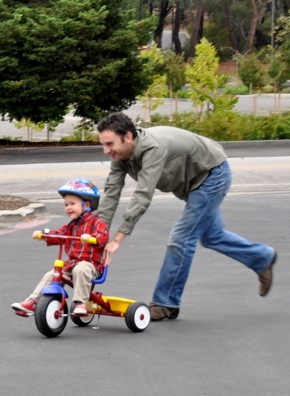 toddler hurries to get his bike blessed at St. Bede's
