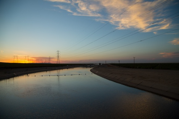 The sun sets behind power towers over the California Aqueduct near highway 41 in the Central Valley.