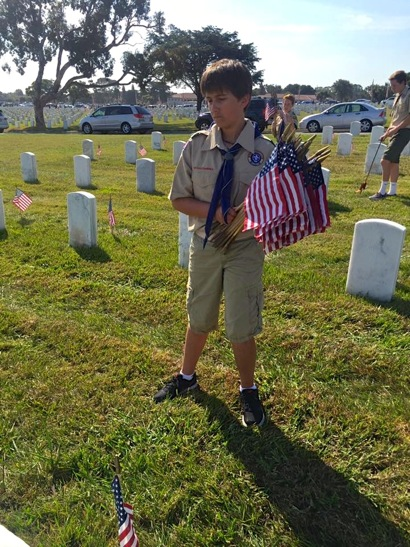 Scout placing flags at headstones