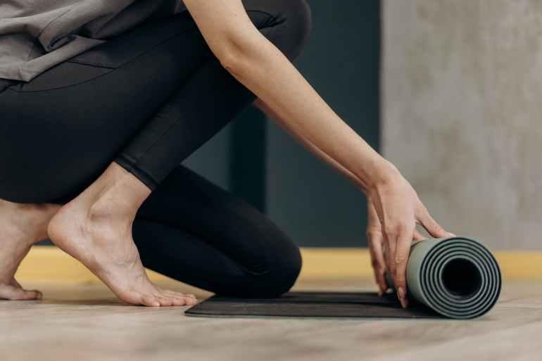 woman unrolling a yoga mat