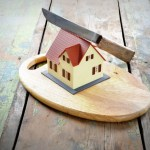 House on chopping board with knife showing the concept of the dividing up assets in divorce or separation