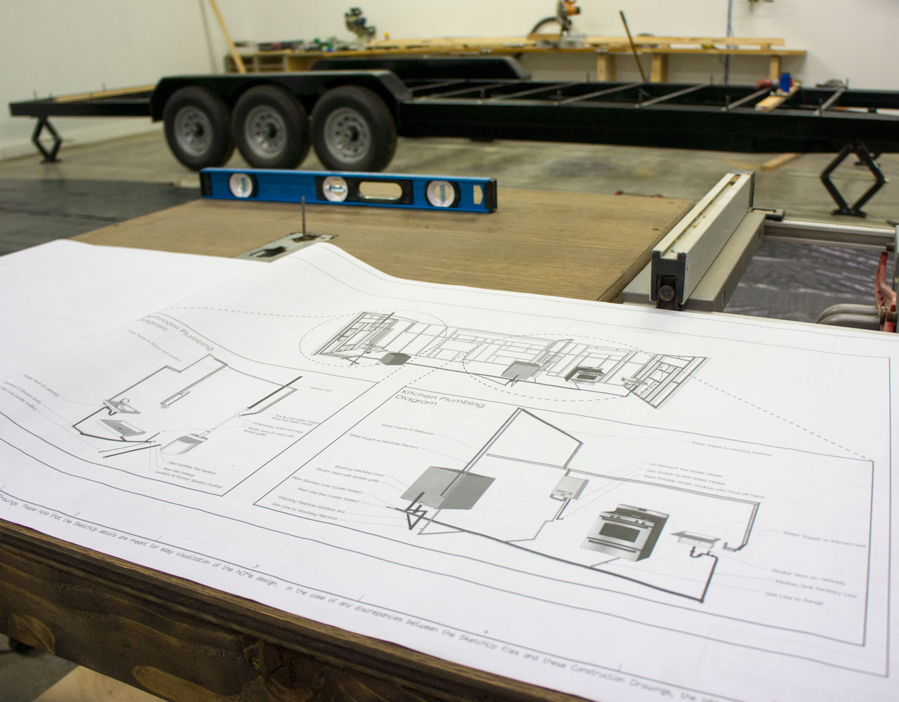 Plans for the construction of a custom tiny home, with the trailer for the tiny house in the background