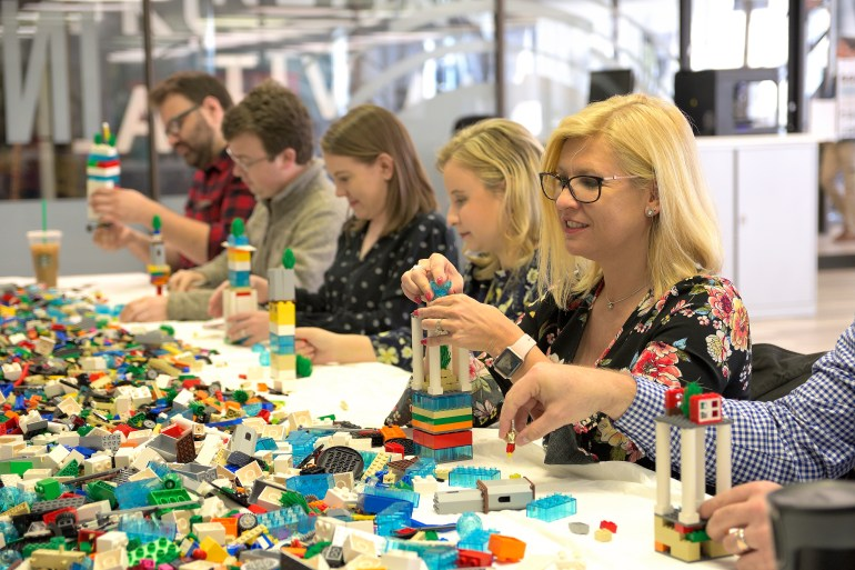 People at a table building LEGO structures