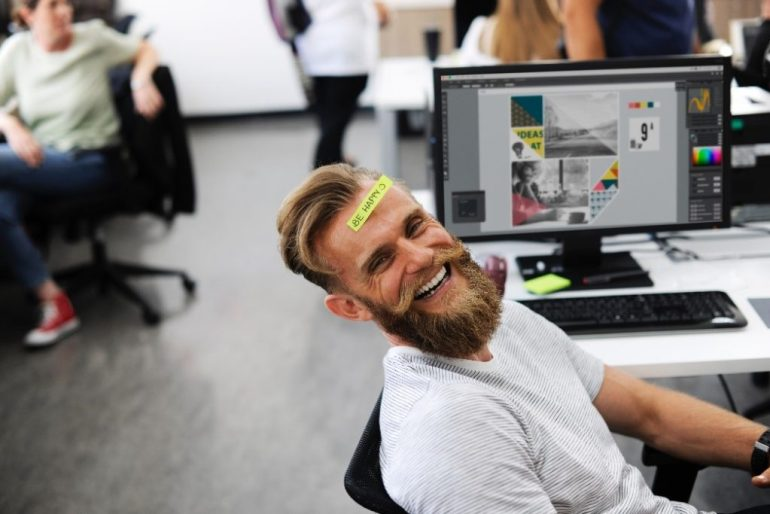 man laughing at his desk