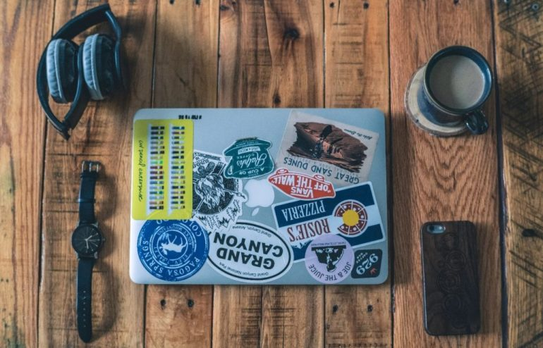 laptop with stickers with a watch, earphones, coffee and phone