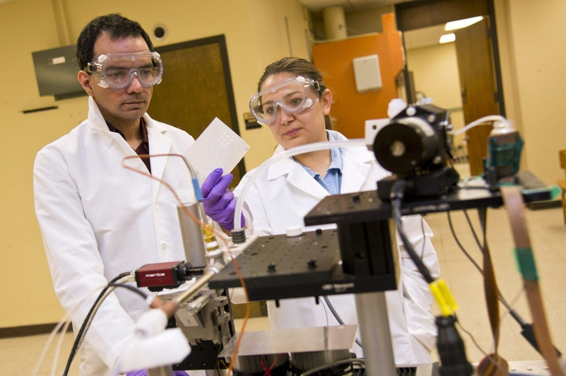 Arun Giridhar, an associate research scientist in Purdue's School of Chemical Engineering, works with student Sierra Davis to operate a prototype system to dispense precise medication dosages tailored for specific patients, an advance in personalized medicine that could improve drug effectiveness and reduce adverse reactions. (Purdue University photo/Steven Yang)