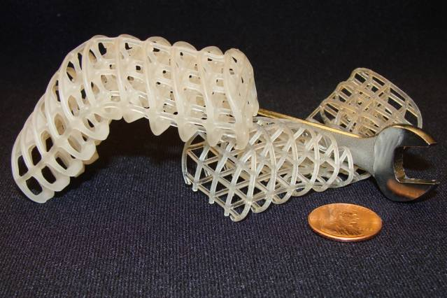 Two 3D-printed soft, flexible scaffolds: The one on the left is maintained in a rigid, bent position via a cooled, rigid wax coating, while the one on the right is uncoated and remains compliant (here, it collapses under a wrench). Courtesy of the researchers