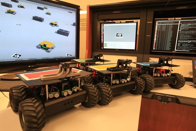 """The four """"Swarmies"""" robots on a table with the software simulation used to develop the program to control the robots. Image Credit: NASA/Dmitri Gerondidakis"""