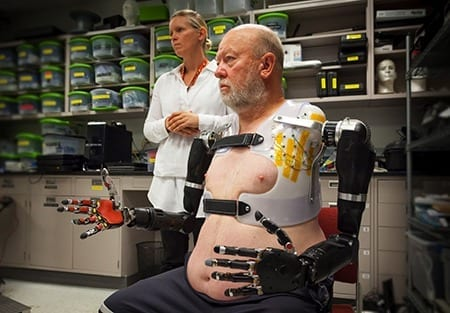 APL prosthetist Courtney Moran looks on as Les Baugh tests out the Modular Prosthetic Limbs.