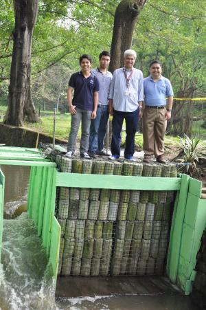 The dam's frame consists of gabion cages: wire mesh baskets filled with sturdy columns of recycled concrete cylinders or rocks