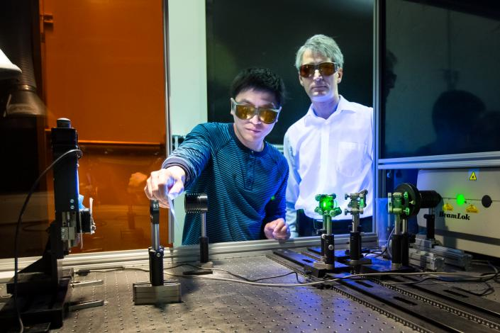 Adrian Sabau and Jian Chen work with a laser to prepare the surface of carbon fiber composites and aluminum to create superior bonds that can absorb 200 percent more energy than conventional bonds.