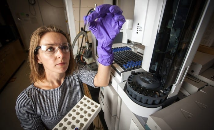 Lawrence Livermore National Laboratory chemist Sarah Baker holds a gas chromatography vial used to measure the amount of methanol produced by the enzyme-embedded polymer. Photos by George Kitrinos/LLNL