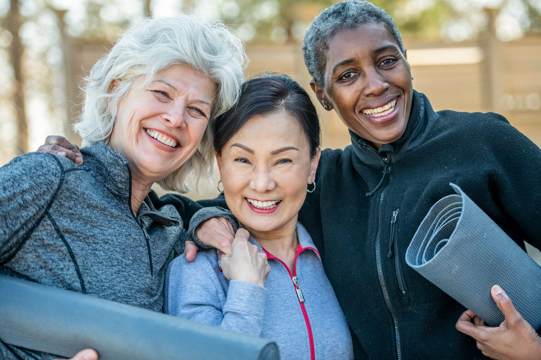3 women smile after exercising together in the park.