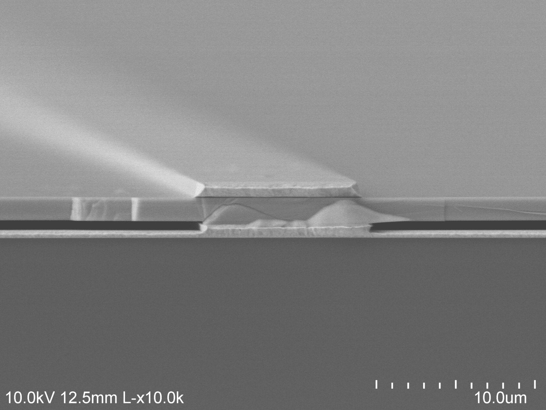The electron microscope image shows the air (darkest gray) sandwiched between the gold backing at the bottom and the semiconductor at the top, supported on gold beams. Image credit: Dejiu Fan, U-M Optoelectronic Components and Materials Group