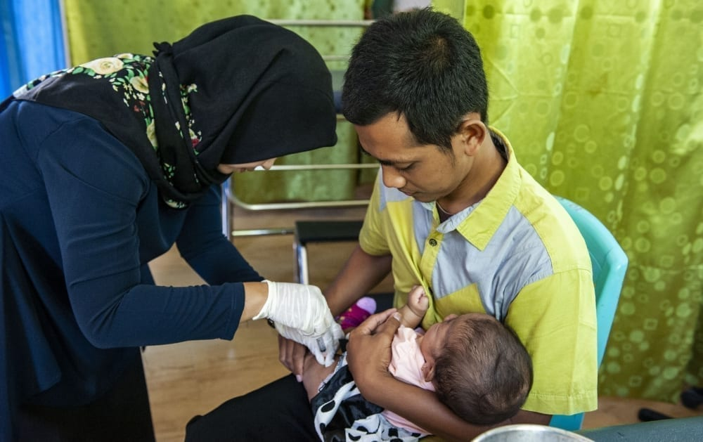A nurse gives a baby an immunization at a healthcare clinic on the edge of the Gunung Palung National Park in West Kalimantan, Indonesia
