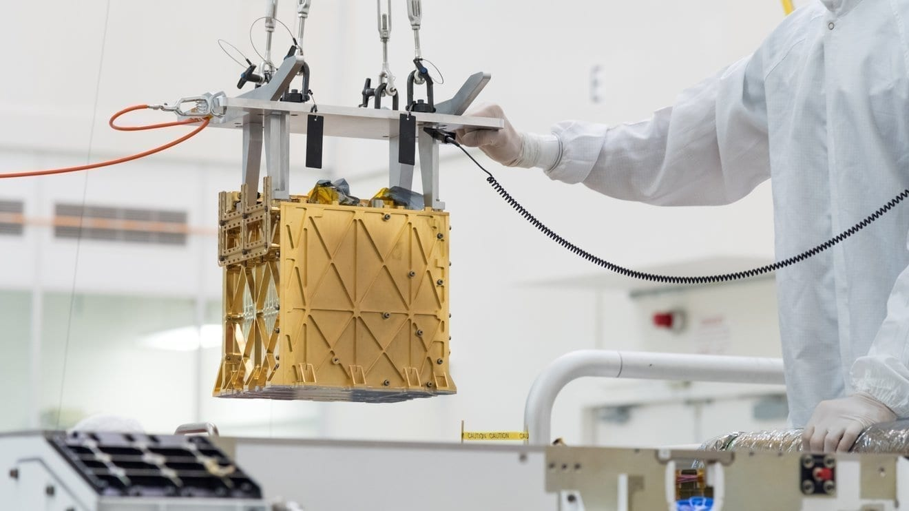 Technicians at NASA's Jet Propulsion Laboratory lower the Mars Oxygen In-Situ Resource Utilization Experiment (MOXIE) instrument into the belly of the Perseverance rover. Credit: NASA/JPL-Caltech