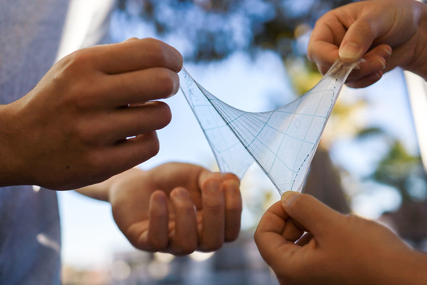 Lab mates in the Bao Research Group at Stanford demonstrate the flexibility and stretchability of their artificial skin made using their newly created printing method. (Image credit: Yuqing Zheng)