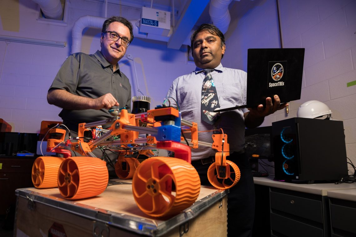 University of Arizona engineering faculty members Jekan Thanga (right) and Moe Momayez have received $500,000 in NASA funding for a new project to advance space mining methods that use swarms of autonomous robots. They are pictured with a low-cost, rapidly designed, 3D-printed rover prototype used for testing a new generation of miniature sensors for applications in lunar mining.Chris Richards/University of Arizona