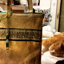 Sophie's cat Galipette posing next to her ladies' bag creation