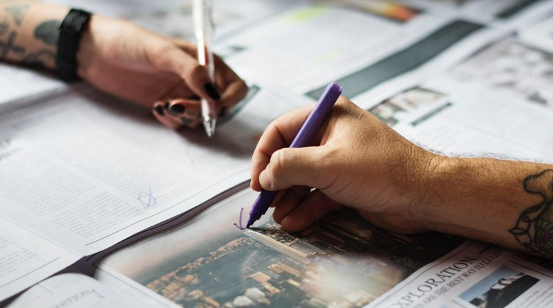 Image of hands writing on newspaper