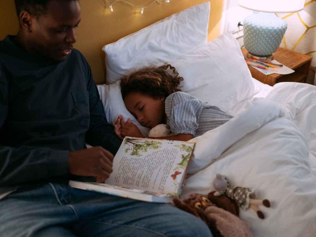 father reading bedtime story for his daughter while lying down on the bed