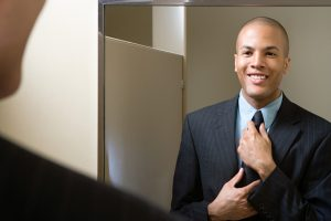 Man adjusting tie in mirror