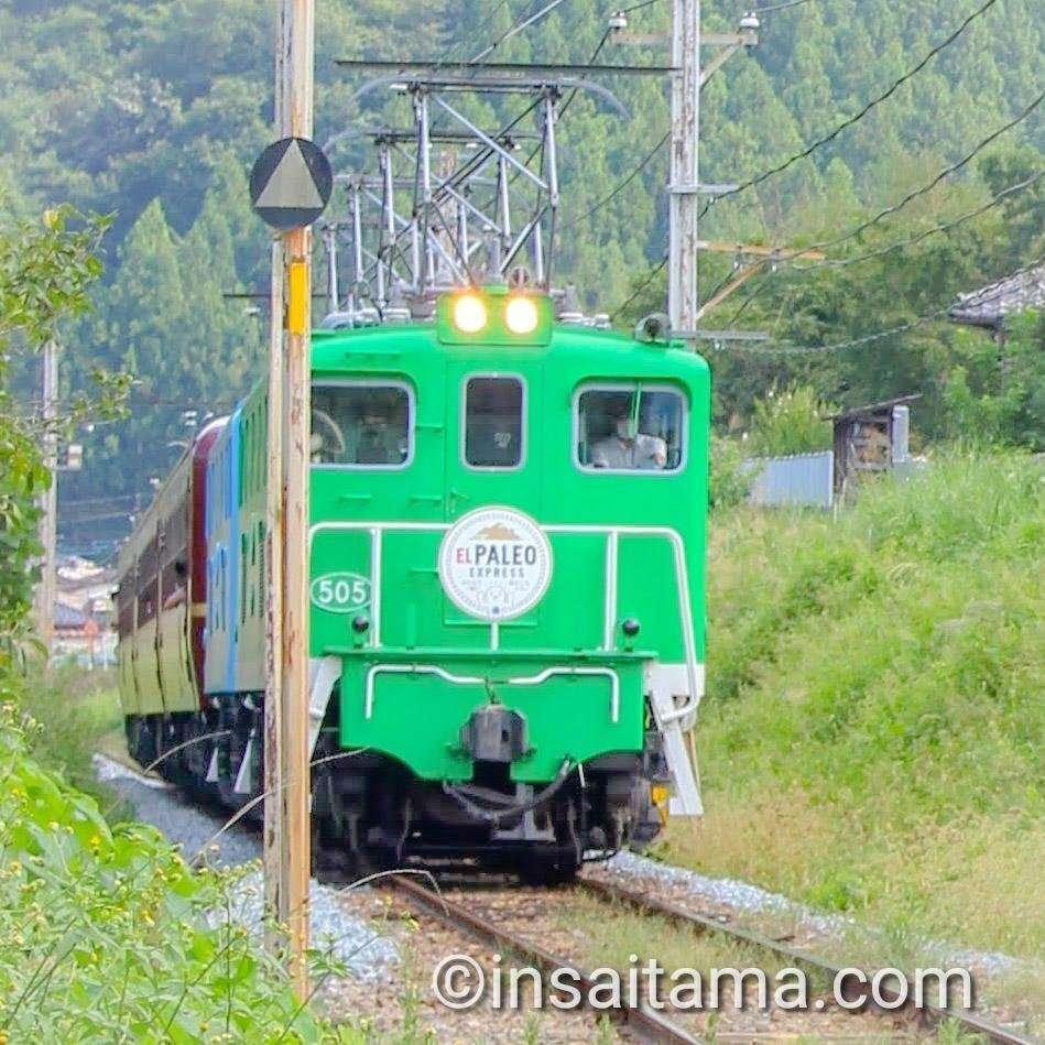 electric locomotive paleo express passing through arakawa roadside station