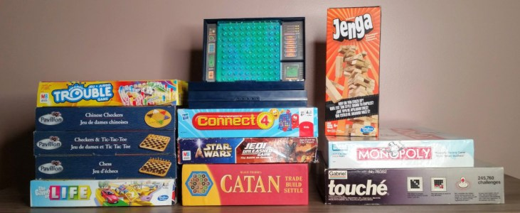 A stack of board games to be played and decluttered during the October Use It Up Challenge.