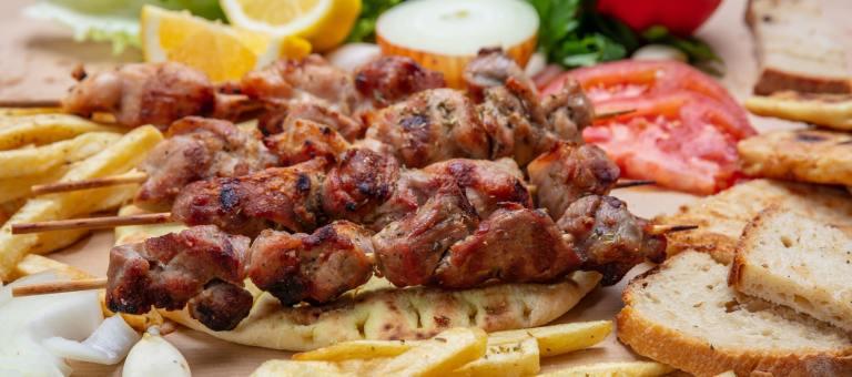 Souvlaki, meat skewers, traditional greek turkish meat food on pita bread and potatoes