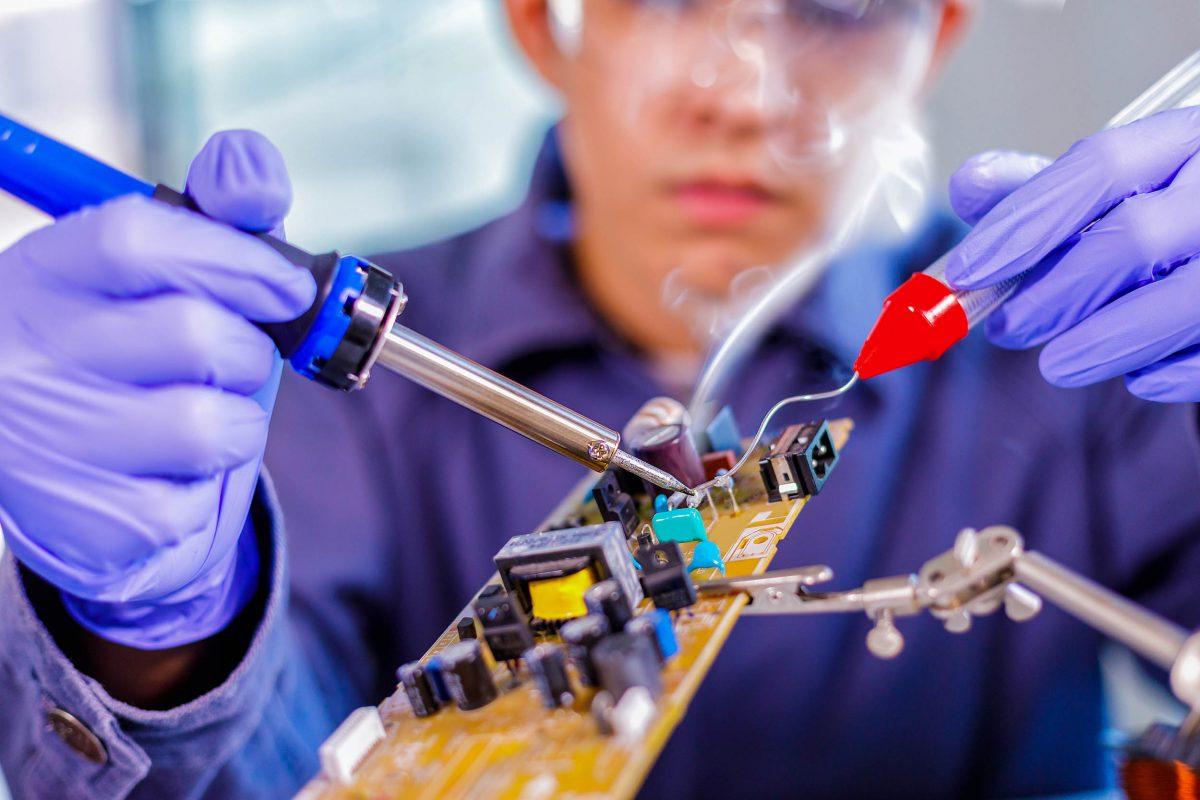 Engineer or technician repair electronic metal detector circuit board
