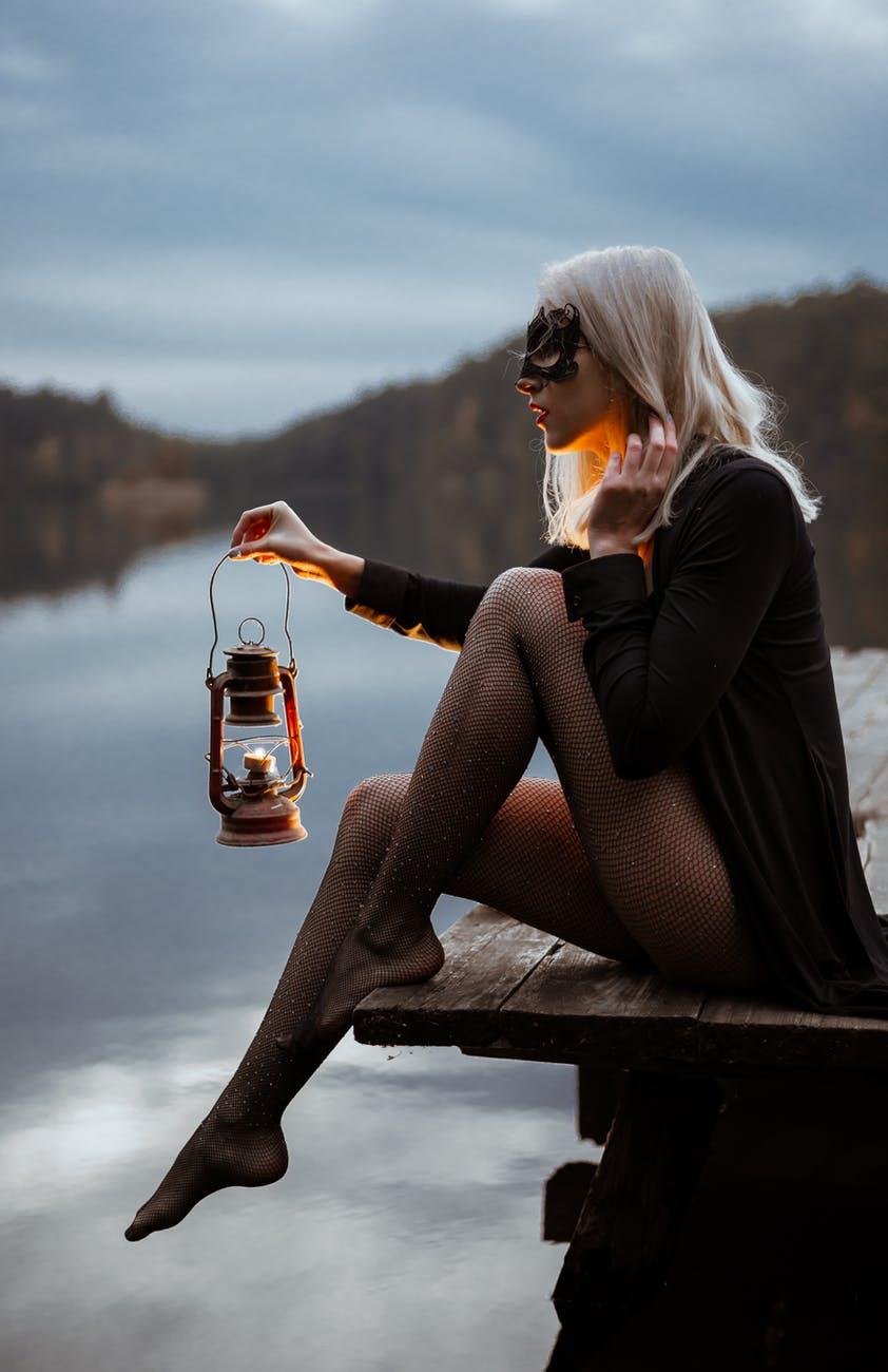 trendy woman with lantern on pier near lake