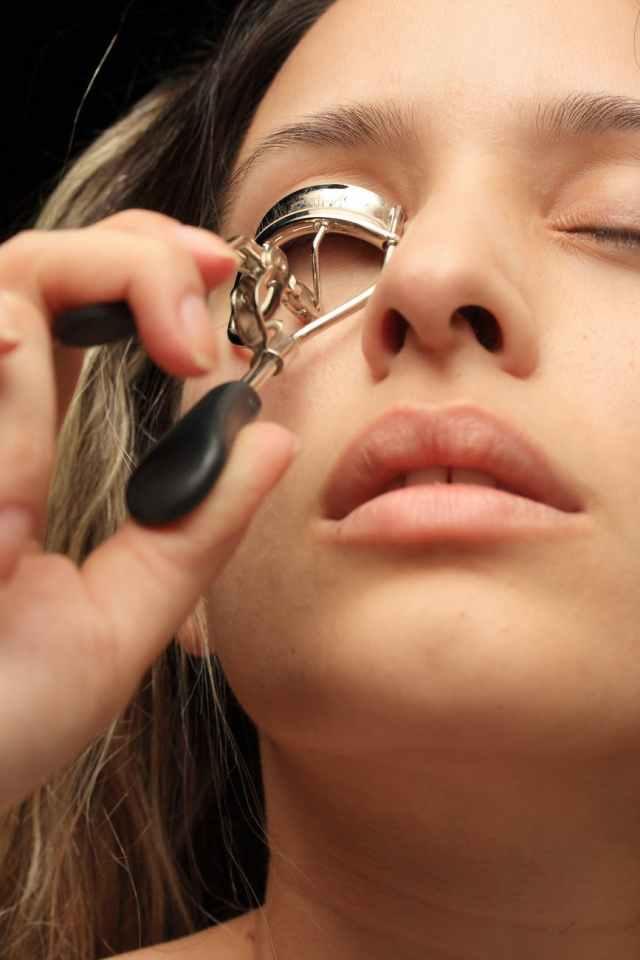 woman using eyelash curler close up photography