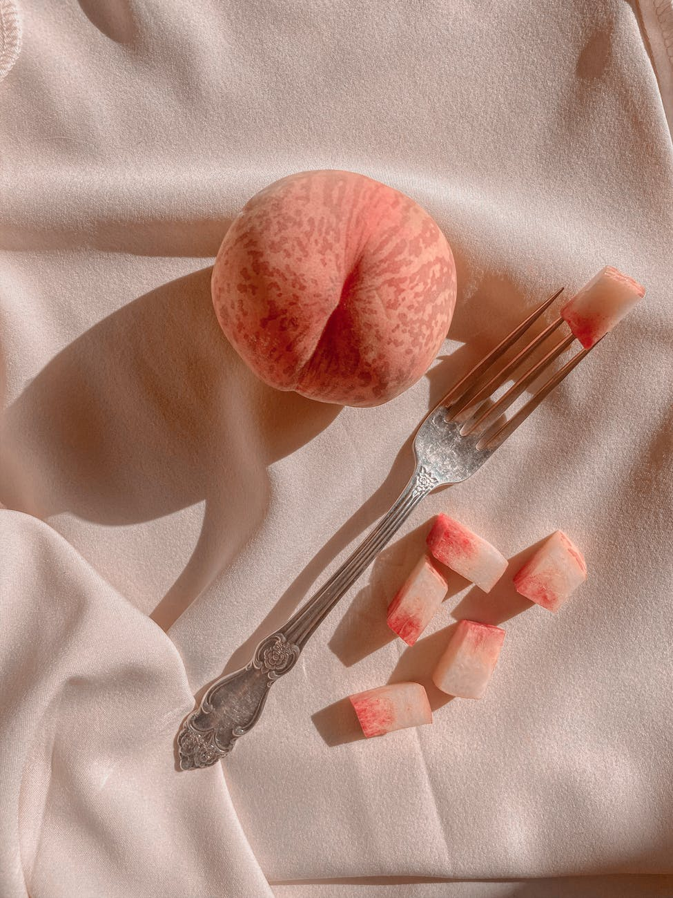 ripe peach with fork on draped fabric