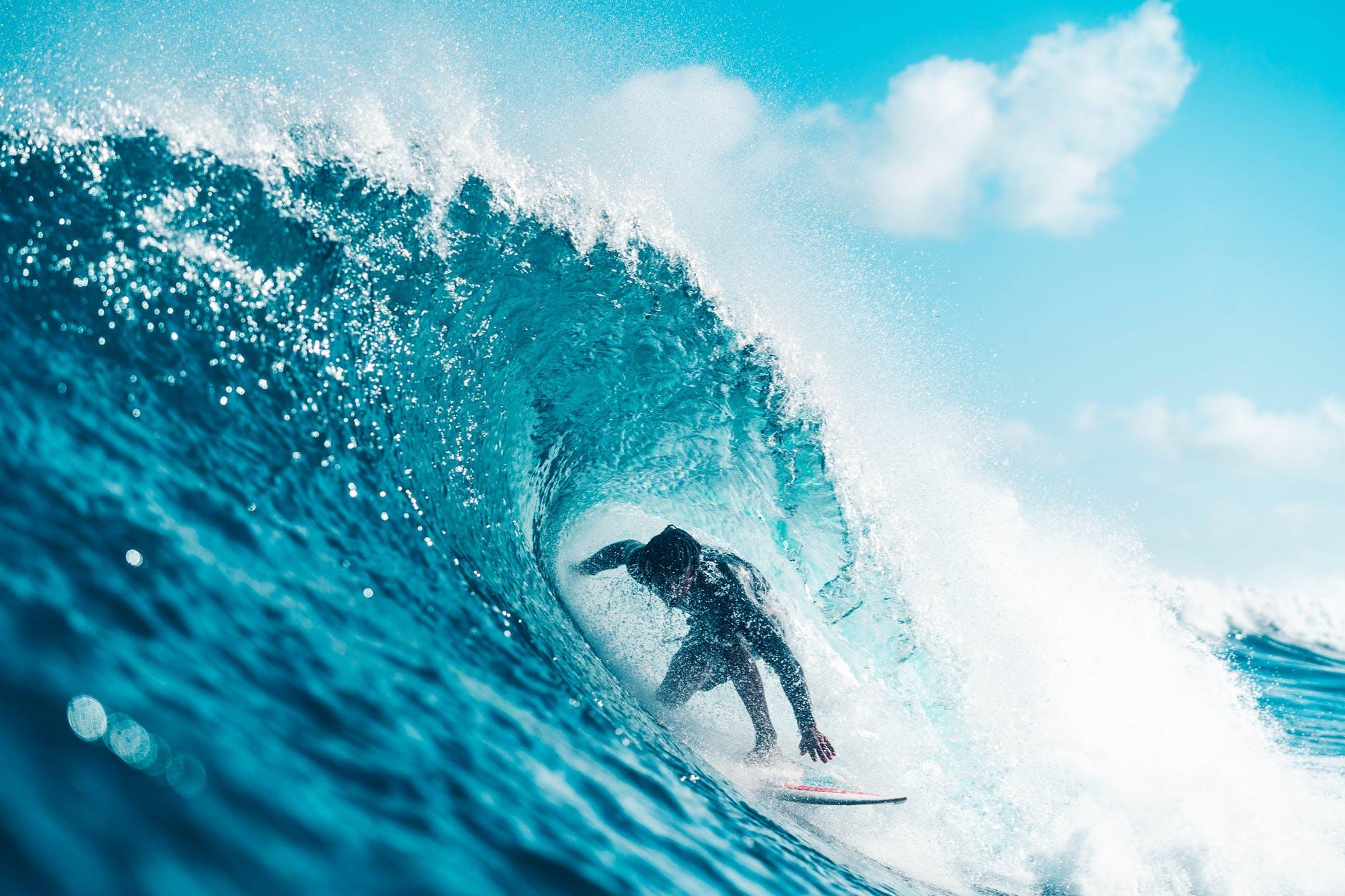 unrecognizable energetic surfer riding azure sea wave