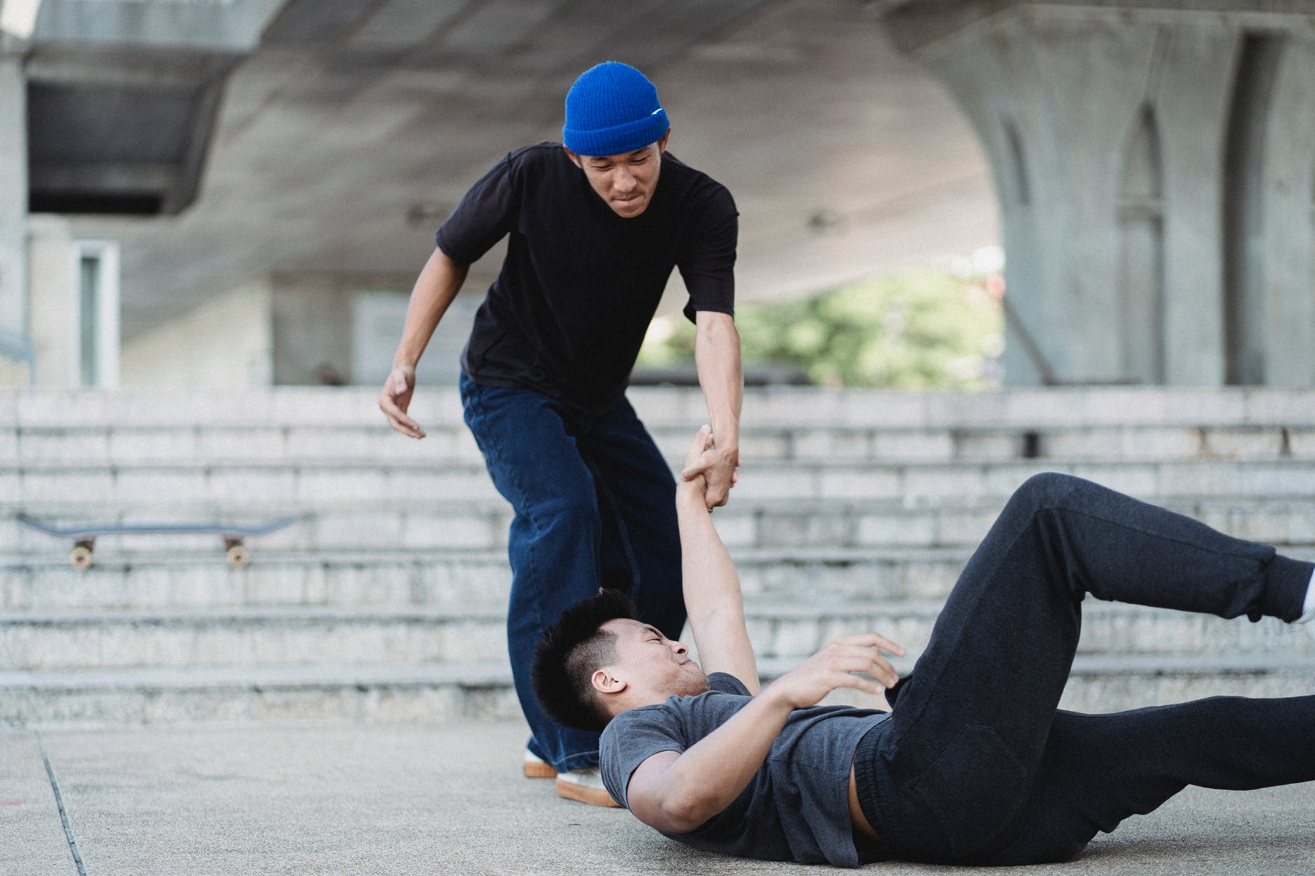 young asian man helping friend on pavement
