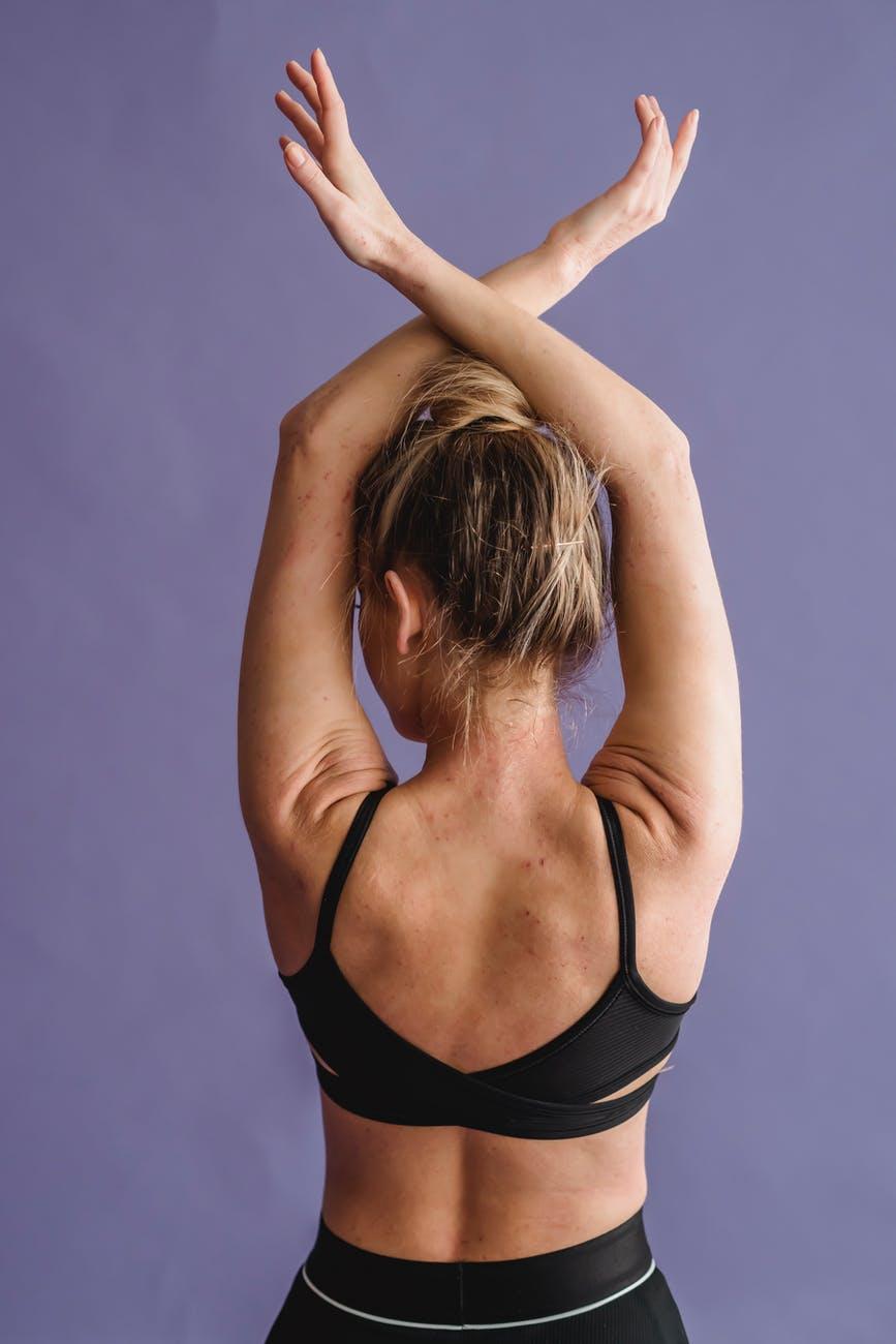 fit woman raising crossed arms in studio