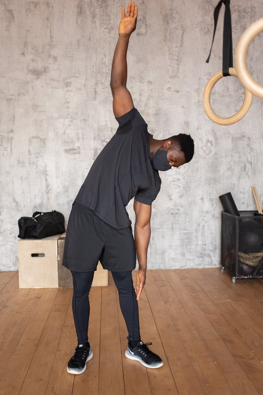 black man in mask doing exercises in gym