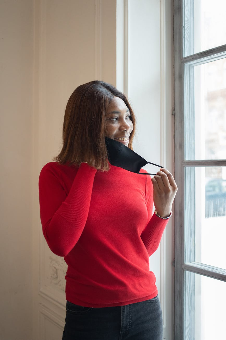 smiling black woman putting on mask in light room