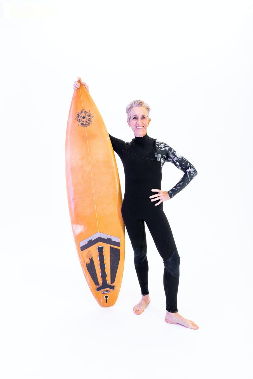 elderly woman holding an orange surfboard