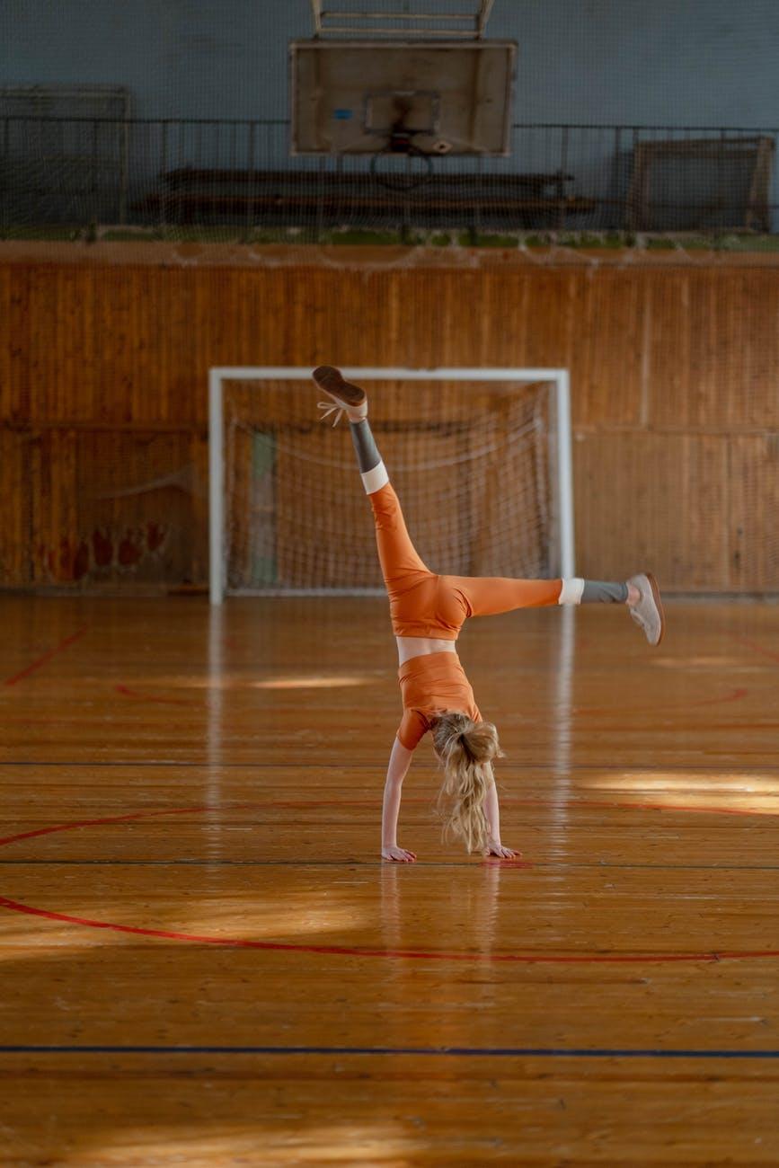 woman in orange sports wear doing cartwheel