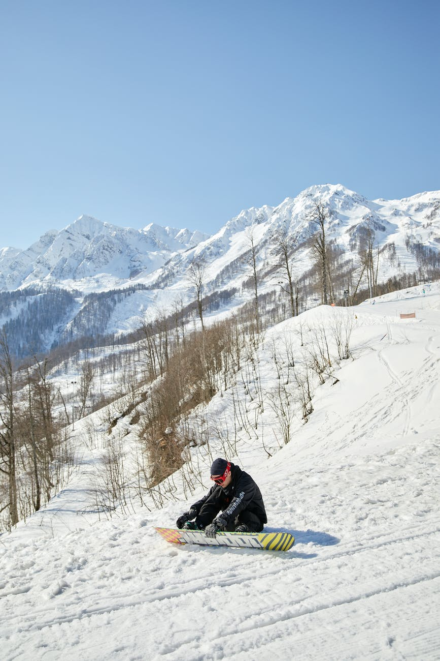 a snowboarder putting on his snowboard