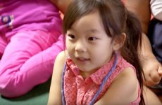 Young student sitting in classroom on floor.
