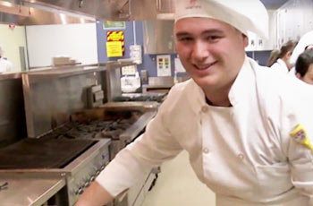 Career Pathways: Student wearing chef hat working in a kitchen