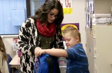 Paraeducator assisting young student with backpack.