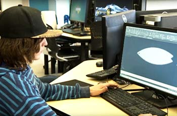 Student working on 3D modeling computer program.